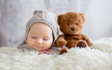 baby boy dressed in overall with a toy bear on bed