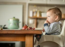 baby sitting on a high chair that attaches to table