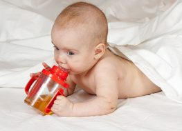 baby with a baby cereal bottle feeder